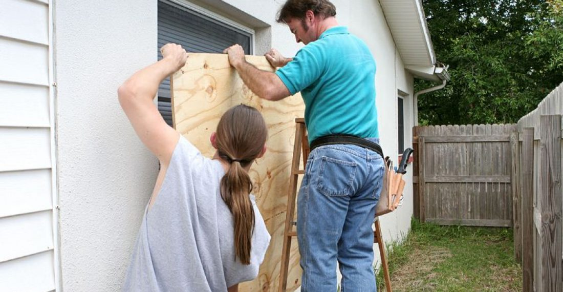 456424 - a father and son working together to install plywood over windows in preparation for a hurricane.